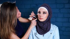 Sminkkonstnären gör ett ljust smink för en arabisk kvinna som bär en sjalett arkivfilmer