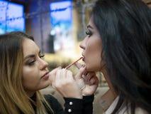 Sminkkonstnären gör makeup till den härliga unga kvinnan inomhus yrkesmässiga målarfärgkanter med läppstift fotografering för bildbyråer