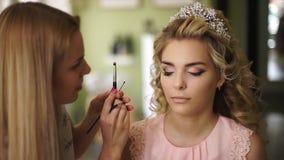 Sminkkonstnären målar framsidan av bruden, i en härlig salong Yrkesmässig makeup för kvinna med sunt barn vänder mot stock video