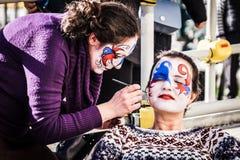 Sminkkonstnären målar framsidor på den Venedig karnevalet Royaltyfria Bilder