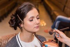 Sminkkonstnären sätter smink på modell Royaltyfria Bilder