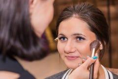 Sminkkonstnären sätter smink på modell Royaltyfri Foto