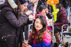 Sminkkonstnärer målar framsidor av turister på den Venedig karnevalet Royaltyfri Bild