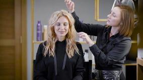 Sminkprocess, framsidan av en härlig ung kvinna och makeupkonstnärs hand med en borste och en svamp lager videofilmer