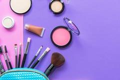 Sminkprodukter som spiller ut ur skönhetsmedel för en pastellblått, hänger löst, på purpurfärgad och rosa bakgrund med tomt utrym arkivfoton