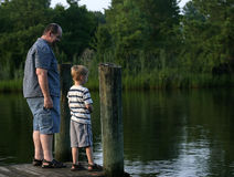 Smirk. A father and son talking at the end of a pier Royalty Free Stock Photography