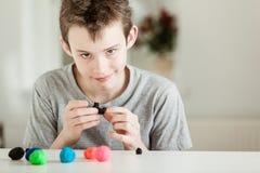 Smirking Kind, das mit Stücken Lehm spielt lizenzfreies stockbild