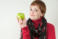 Smirking woman holding green apple Stock Images