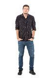Smirking young casual man wearing jeans and plaid shirt with hands in pockets. Stock Image