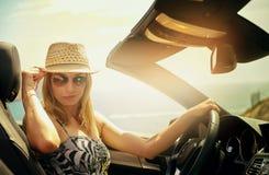 Smirkings jonge vrouw bij stuurwiel Stock Foto's