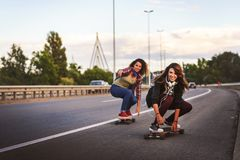 SmiSkateboard girls riding longboards down the road Stock Images
