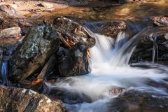 Smith Creek at Anna Ruby Falls near Helen Georgia USA. Autumn leaves add color to the wet rocks that surround the fast flowing. Small waterfall. Focus on royalty free stock image