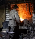 The smith is fanning a burning furnace. The concept of manual labor and the creation of a new product stock image