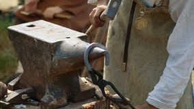 The smith forges a horse horseshoe. Blacksmith work. Blacksmith beats a piece of hot metal with a hammer on an anvil. The smith forges a horse horseshoe stock video