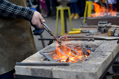 The smith heats a metal detail in a forge brazier.  Royalty Free Stock Photo