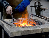 The smith heats until red a metal detail in a forge brazier.  Stock Photography
