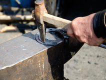 The smith. Making forges a horseshoe on an anvil Royalty Free Stock Images