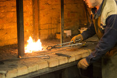 The smith in a smithy. The smith works in a smithy for fire Royalty Free Stock Image