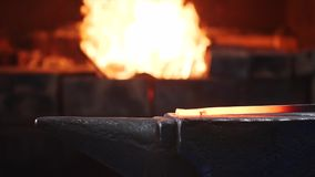 Blacksmith hitting hot metal bar with massive hammer on anvil in slow motion.