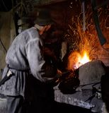 The smith is working near the burning furnace. The concept of manual labor and the creation of a new product royalty free stock image
