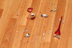 Smithereens of crushed red Christmas ball on floor. Smithereens of crushed red Christmas ball on clean wooden floor Stock Photo