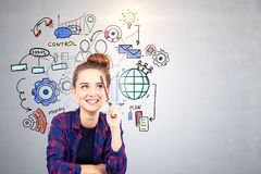 Cheerful teen girl business management icons. Smling hipster teen girl in checkered shirt sitting near concrete wall with colorful management and business stock photo