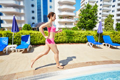 Smling woman in pink sportswear runs along pool Stock Photos