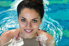 Smling woman swimming in the swimming pool at the hotel spa Stock Image