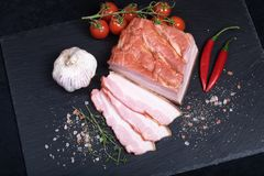 Smocked bacon on black stone plate. Close up of smocked bacon on black stone plate with garlic, chilli and cherry tomatoes royalty free stock image