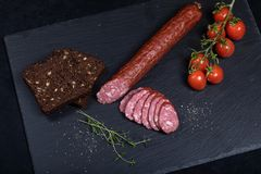 Smocked sausage on black stone plate. Close up of smocked sausage with bread and cherry tomatoes stock photo