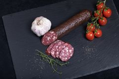 Smocked sausage on black stone plate. Close up of smocked sausage with garlic and cherry tomatoes royalty free stock photography