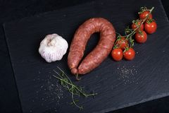 Smocked sausage on black stone plate. Close up of smocked sausage with garlic and cherry tomatoes stock images
