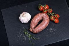 Smocked sausage on black stone plate. Close up of smocked sausage with garlic and cherry tomatoes royalty free stock images
