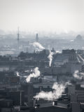 Smog - city air pollution. Unclear atmosphere polluted by smoke rising from the chimneys. Stock Photos