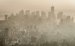 Smog over Manhattan, New York. Manhattan, New York, a cityscape with skyscrapers appearing out of the smog caused by air pollution Royalty Free Stock Photos