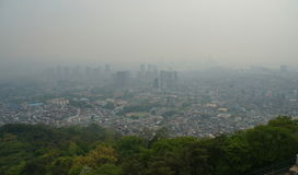 Smog over Seoul City, South Korea. Skyline of downtown Seoul behind green vegetation with dense man-made smog obstructing the view. Seoul, View from Namsan Royalty Free Stock Photo