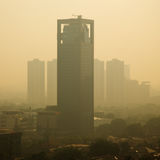 Smog Sunrise. High rise building at sunrise – in a polluted city, the smog dampens color and makes the air semi-opaque Royalty Free Stock Images