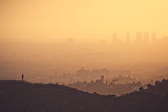 Smoggy Los Angeles. A man walks in the hollywood hills with a cityscape in the background stock photography
