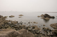A smoggy view from Yantai China. The rocky coast of Yantai China and a smoggy view of the industrial area across the bay Stock Photo