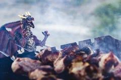 Smok jest kucharz piec mięsem Zdjęcia Stock