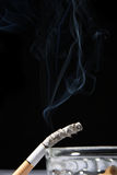 Smoke. A burning cigarette with black background royalty free stock image