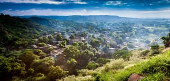 A village on Hill. Smoke arising out of every house of a hamlet with first ray of sun indicates that peoples are preparing their breakfast Royalty Free Stock Photos