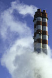Smoke around tall chimneys. Clouds of white smoke around tall industrial chimneys Royalty Free Stock Images