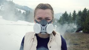 Smoke around. Teen in gas mask looks at camera in nature. Smoke is around. Teen in gas mask looks at camera in nature forest. Winter stock video footage