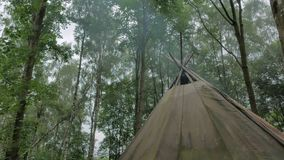 Smoke bellowing from a tipi forest stock video footage