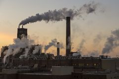 Smoke billowing out of several old paper mill industrial buildings royalty free stock photography
