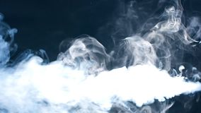 Smoke on black background in blue light.