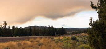 Long Panoramic Cascade Mountain Range Forest Wildfire. Smoke blocks out the sun and The Cascade Mountain Range Mt Jefferson Ranch land royalty free stock image