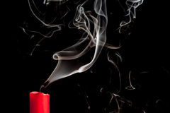 Smoke from blown out red candle. On black backround stock photography