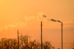 Smoke from the boiler pipes at sunset. Winter landscape Stock Photography